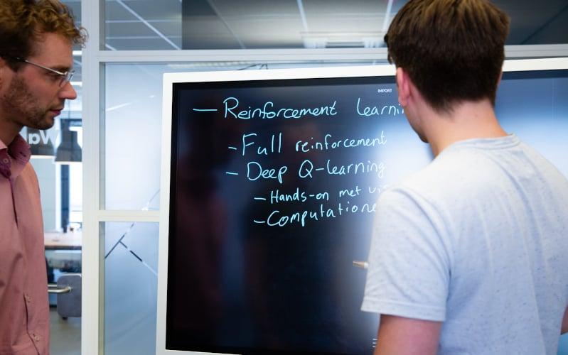 '2 heren die op een whiteboard reinforcement learning behandelen'