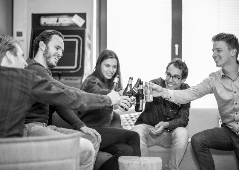 'Zwart-wit foto van collega's die samen borrelen'