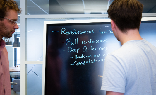 '2 heren die op een whiteboard reinforcement learning behandelen'