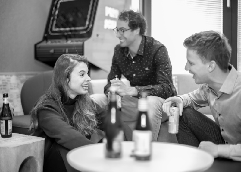 'Zwart-wit foto van collega's die lachen en borrelen'