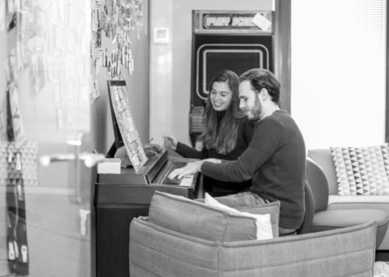 'Zwart-wit foto van heer en dame die piano spelen'